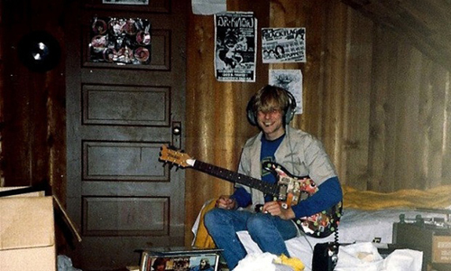 In this undated photo provided by Kim Cobain, a young Kurt Cobain plays guitar in his childhood home in Aberdeen, Wash.  Cobain's mother, Wendy O'Connor, is putting the 1.5-story Aberdeen bungalow _ which is assessed at less than $67,000 _ on the market for $500,000. But she'd also be happy entering into a partnership with anyone who wants to turn it into a museum. (AP Photo/Courtesy Kim Cobain)